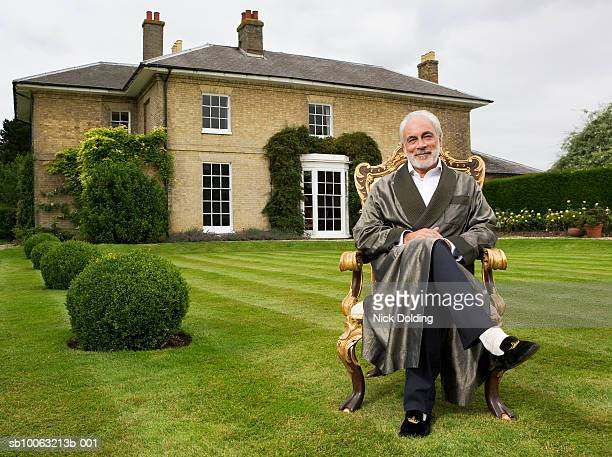 Senior man sitting on antique chair in garden, smiling. Looking at camera