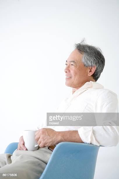 Senior man sitting on armchair, holding coffee cup