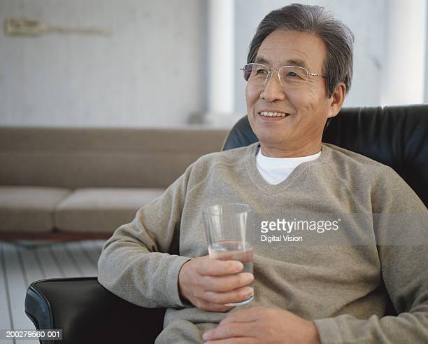 Senior man sitting on armchair holding glass of water, smiling