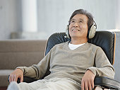 Senior man sitting on armchair wearing headphones, smiling