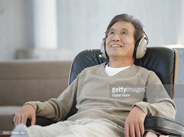 老人男性が座っている笑顔を着て、ヘッドフォン、アームチェア