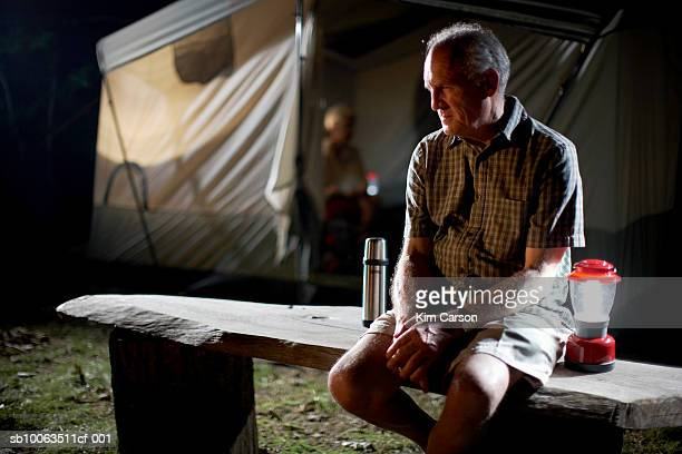 Senior man sitting on bench outside tent at night