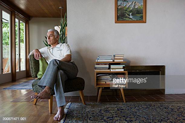 Senior man sitting on chair, looking away