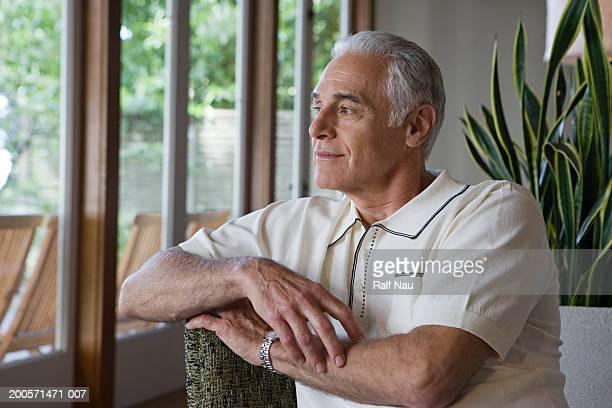 Senior man sitting on chair, looking away, smiling