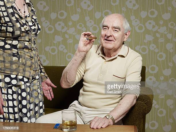 Senior man sitting on couch smoking cigar