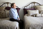 Senior man sitting on edge of bed in double bedroom