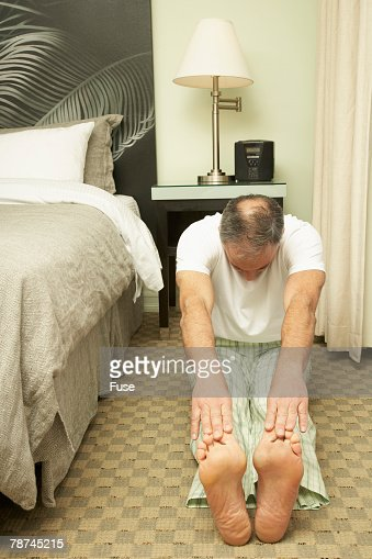Senior Man Sitting On Floor By Bed Touching His Toes Stock