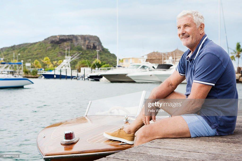 Senior man sitting on jetty : Stockfoto