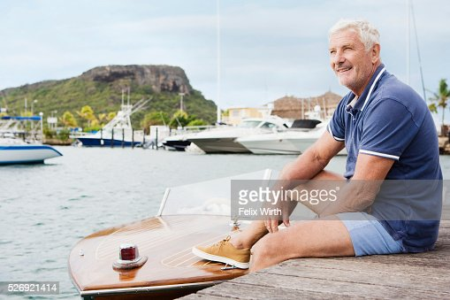Senior man sitting on jetty : Foto stock