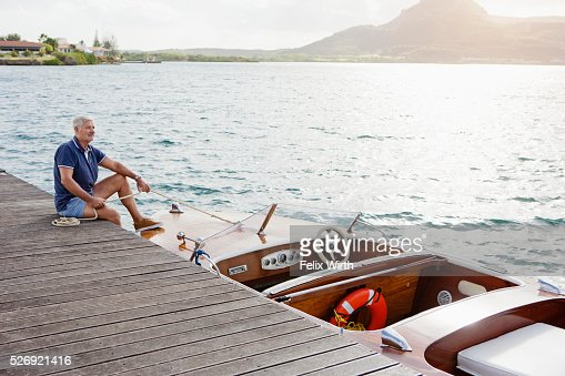 Senior man sitting on jetty with moored motorboat : Stock-Foto