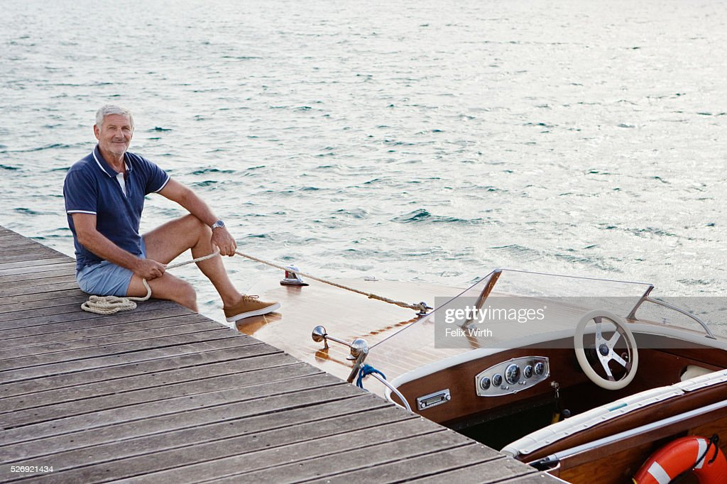 Senior man sitting on jetty with moored motorboat : Stock Photo