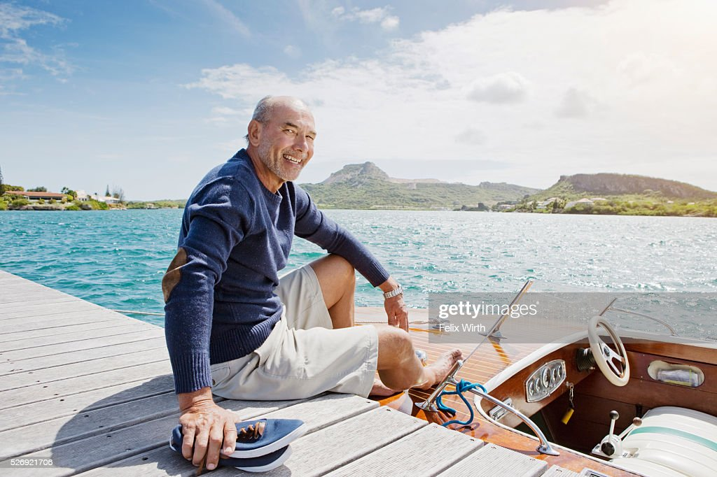 Senior man sitting on jetty with moored motorboat : Photo
