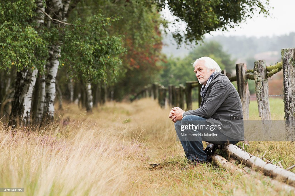 Senior man sitting on log