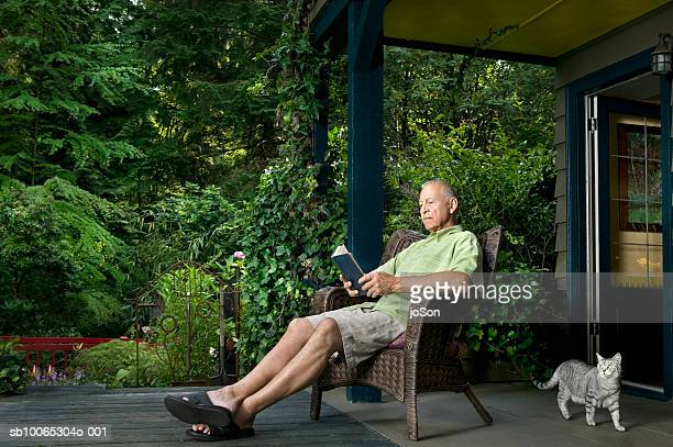 Senior man sitting on porch reading book, cat passing by