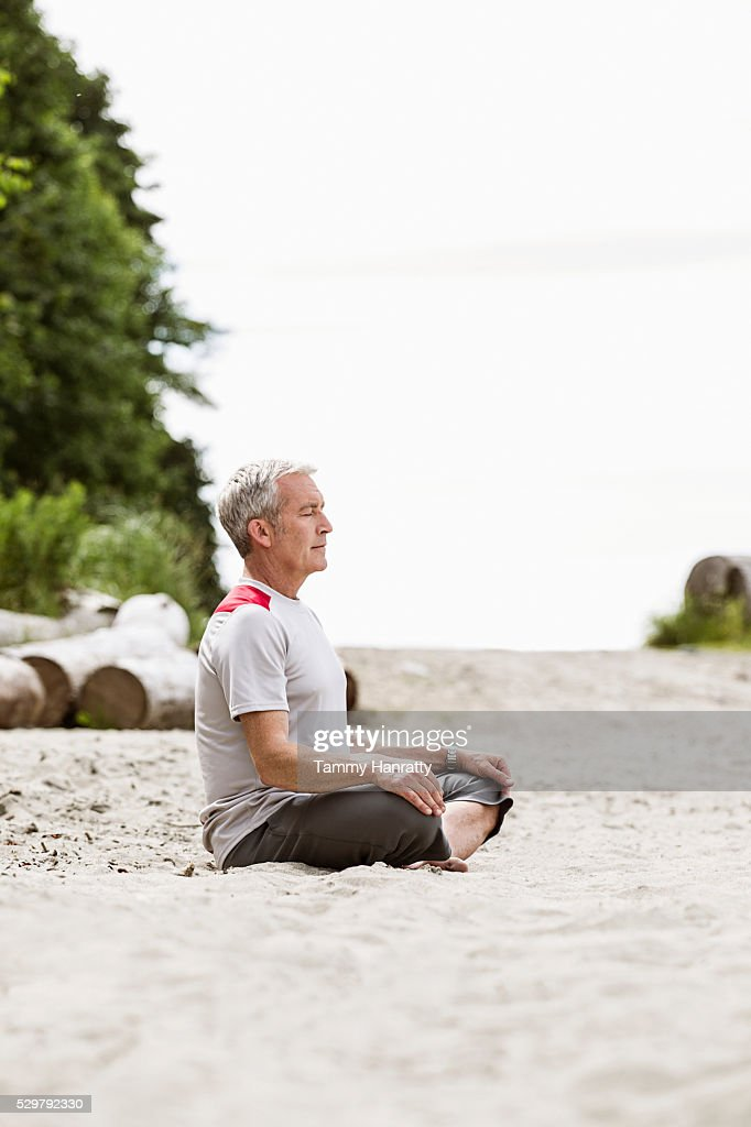 Senior man sitting on sand and practicing yoga : ストックフォト