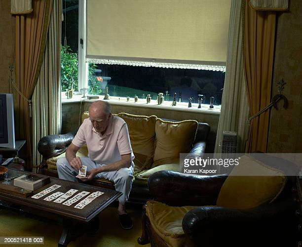 Senior man sitting on sofa, playing cards, elevated view
