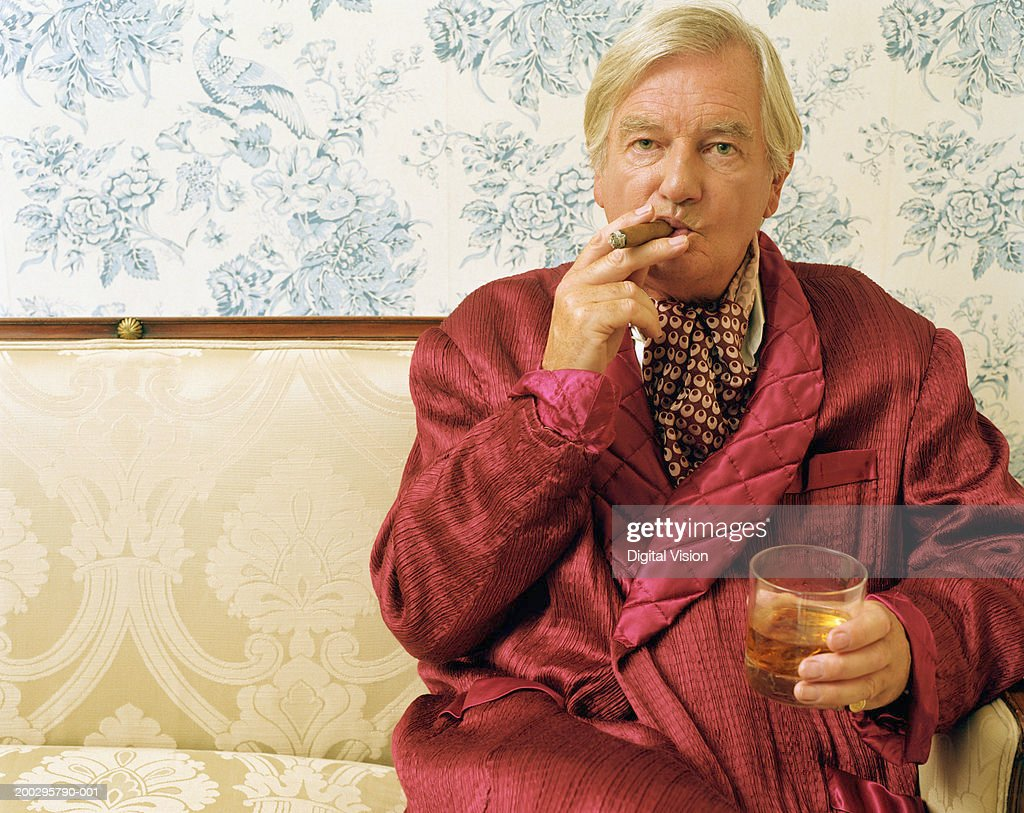 Senior man sitting on sofa, smoking cigar and holding glass, portrait