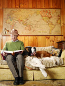 Senior man sitting on sofa with dog, reading book