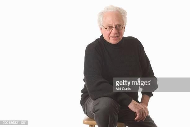 Senior man sitting on stool, smiling, portrait
