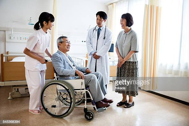 senior man sitting on wheelchair with doctor and woman standing