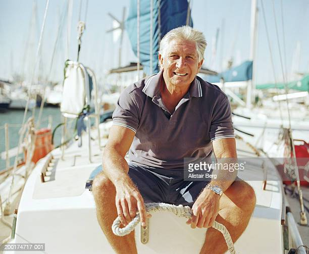 Senior man sitting on yacht, holding rope, portrait (focus on man)