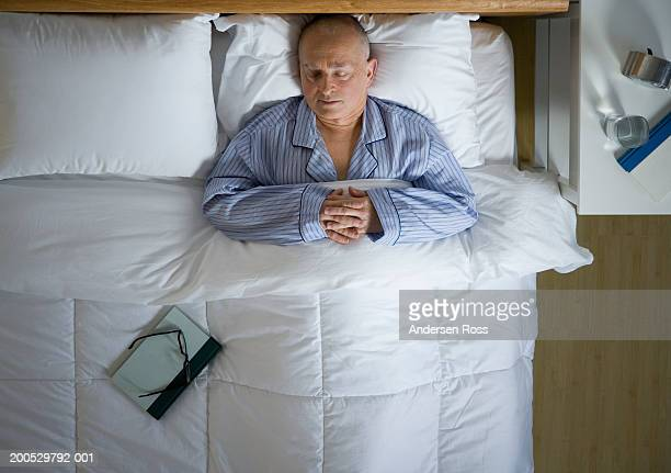 Senior man sleeping in bed, hands clasped, overhead view