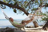 Senior man sleeping in hammock, side view