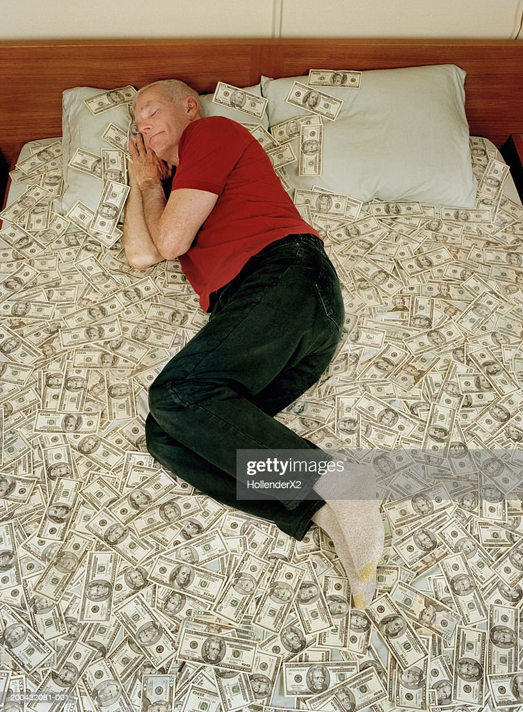 Senior man sleeping on bed covered with US banknotes, elevated view : Stock Photo