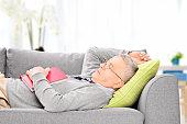 Senior man sleeping on sofa indoors