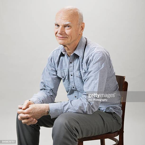 Senior man smiling and sitting in chair