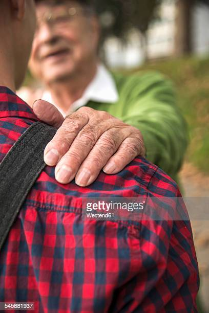 Senior man smiling at adult grandson