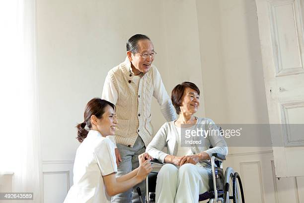 Senior man smiling at senior woman in bed, nurse is by the bed