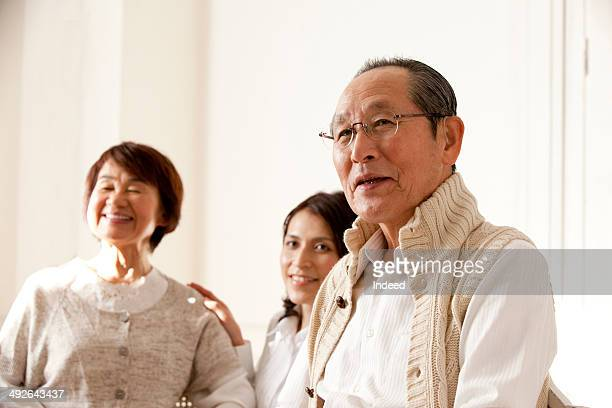 Senior man smiling, his wife and daughter is in behind
