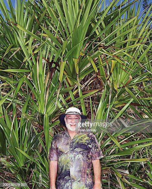 Senior man smiling in front of palm fronds, portrait
