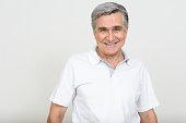 Portrait of Caucasian senior man standing against white background while smiling horizontal studio shot