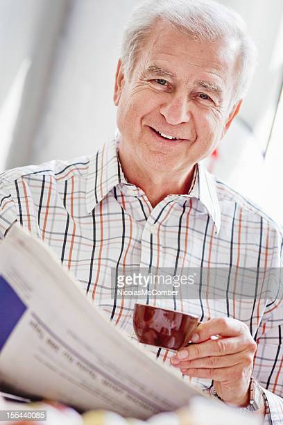 Älterer Mann lächelnd mit Zeitung und espresso