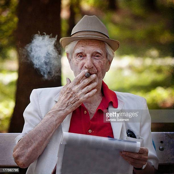 Senior man smoking cigar sitting on a bench in the