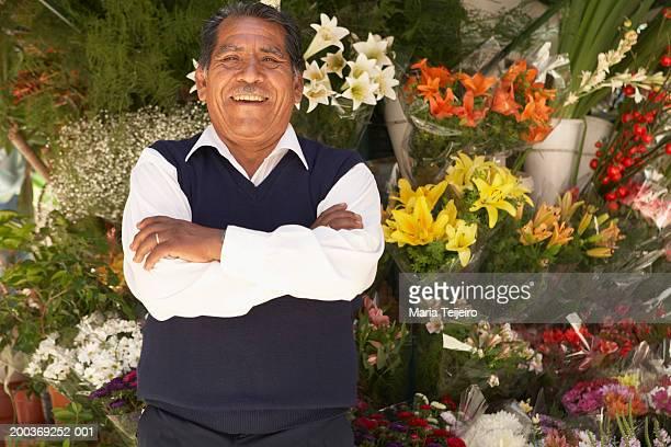 Senior man standing at flower stall in street, smiling, portrait