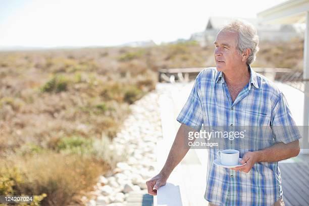 Senior hombre parado en el porche con una taza de té