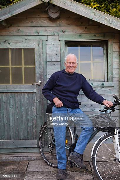 Senior man, standing beside shed with bicycle