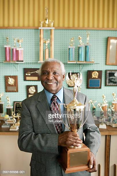 Senior man standing by awards display, holding trophy