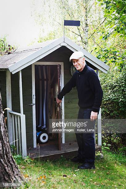 Senior man standing by shed in garden