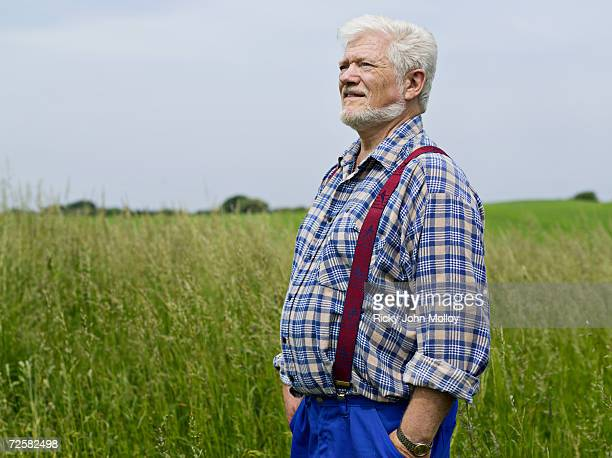 Senior man standing in long grass, side view