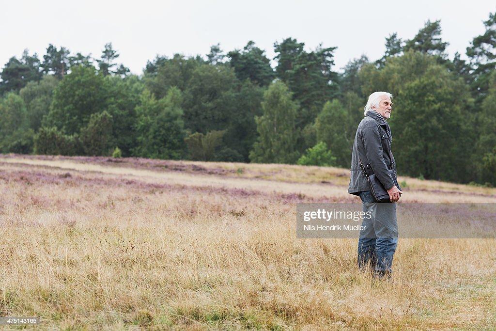 Senior man standing in meadow