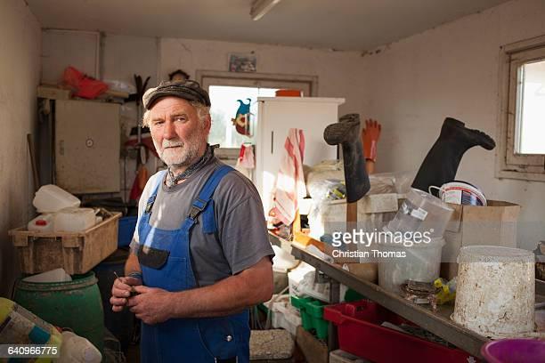 Senior man standing in storage room