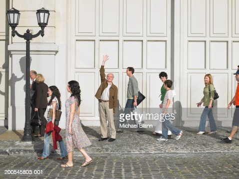 Senior man standing in street with hand raised, portrait