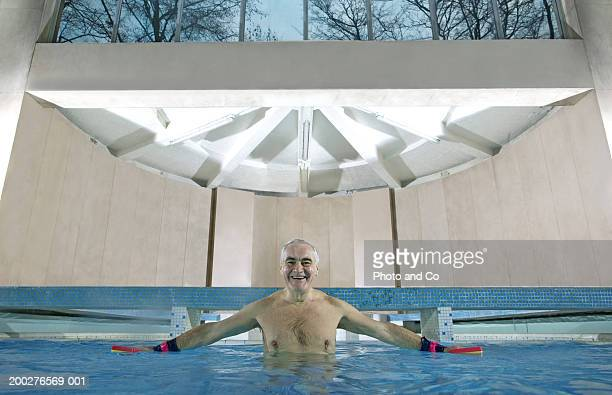 Senior man standing in swimming pool holding floats, smiling, portrait