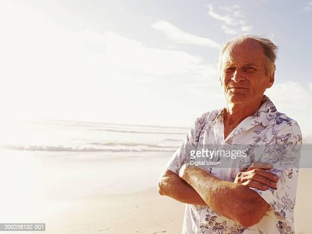 Senior homme debout sur la plage, les bras plié, portrait