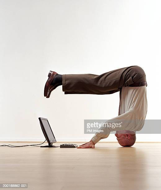 Senior man standing on head, looking at laptop, side view