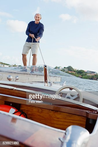 Senior man standing on jetty with moored motorboat : Stockfoto